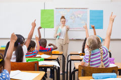 Pupils raising hand during geography lesson in classroom Royalty Free Stock Photos
