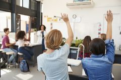 Pupils raising hands in a high school science lesson Stock Photos