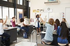 Pupils raising hands in a high school science lesson stock photography