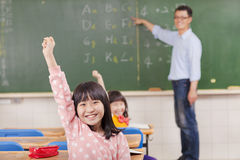 Pupils raising hands during the lesson Royalty Free Stock Photos