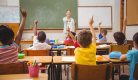 Pupils raising their hands during class Royalty Free Stock Image