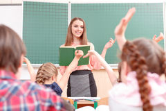 Pupils raising their hands during classes. Be first. Little pupils raising their hands during classes and teacher explaining new material royalty free stock photos