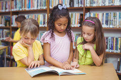 Pupils reading book together in library Stock Images