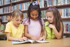 Pupils reading book together in library Stock Photos