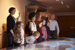 Pupils On School Field Trip To Museum Looking At Map Royalty Free Stock Images