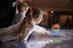 Pupils On School Field Trip To Museum Looking At Map Stock Photos