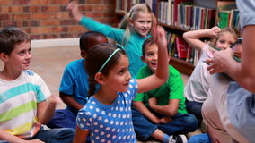Pupils sitting listening to their teacher in the library. In elementary school stock footage