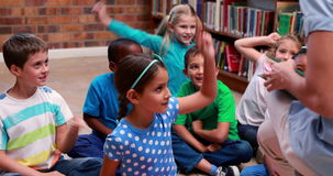 Pupils sitting listening to their teacher in the library. In elementary school stock video footage