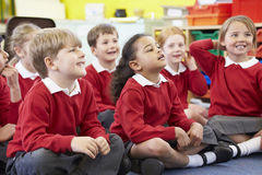 Pupils Sitting On Mat Listening To Teacher Stock Images