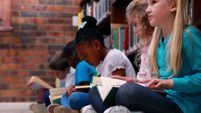 Pupils sitting in a row reading in the library. In elementary school stock footage