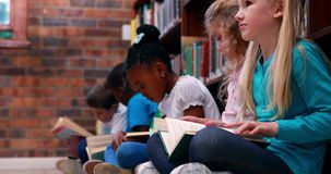 Pupils sitting in a row reading in the library. In elementary school stock video