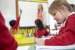 Pupils Sitting At Table As Teacher Stands By Whiteboard Stock Image