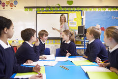 Pupils Sitting At Table As Teacher Stands By Whiteboard Royalty Free Stock Photography