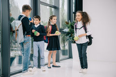Pupils standing in school hallway and having lunch Royalty Free Stock Images