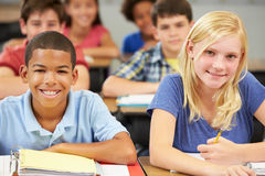 Pupils Studying At Desks In Classroom Stock Photo