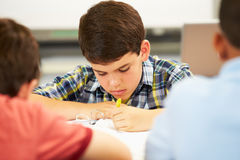 Pupils Studying At Desks In Classroom Royalty Free Stock Photos