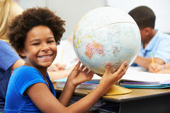Pupils Studying Geography In Classroom. Female pupil holding a globe of the world