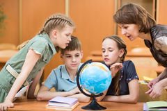 Pupils studying a globe together with teacher Stock Photos
