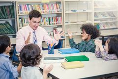 Pupils Studying with teacher At Desks In Classroom,. Teacher and little children sitting discuss about lesson. Young students study in the classroom. Home Stock Image