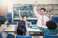 Pupils Studying with teacher At Desks In Classroom,. Teacher and little children sitting lift their hands  up. Young students study ask and answer question in Stock Images