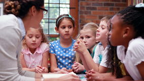 Pupils talking with their teacher in the library. In elementary school stock video