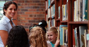 Pupils talking with their teacher in the library. In elementary school stock video footage