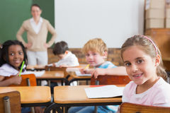 Pupils and teacher smiling at camera in classroom Royalty Free Stock Photos