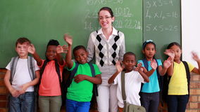 Pupils and teacher waving and smiling at camera in classroom. In elementary school stock video