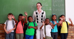 Pupils and teacher waving and smiling at camera in classroom. In elementary school stock video footage
