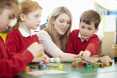 Pupils And Teacher Working With Coloured Blocks Royalty Free Stock Photo