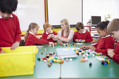 Pupils And Teacher Working With Coloured Blocks Royalty Free Stock Image