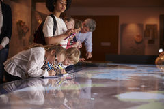 Pupils On Trip To Museum Looking At Map And Making Notes Stock Photos