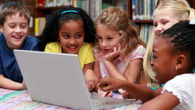 Pupils using the laptop together in the library. In elementary school stock video footage