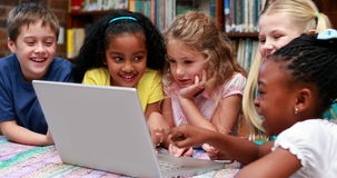 Pupils using the laptop together in the library. In elementary school stock footage