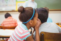 Pupils whispering secrets during class Stock Image