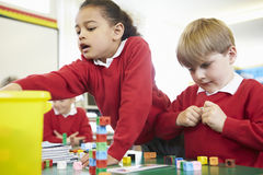 Pupils Working With Coloured Blocks In Maths Lesson Stock Image
