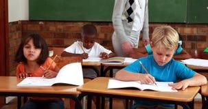 Pupils working while teacher walks around classroom. In elementary school stock video footage