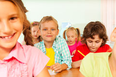 Pupils write in exercise books during lesson Stock Images