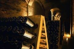 Pupitre en flessen in een ondergrondse kelder stock afbeelding