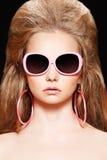 Puppe. Art und Weisebaumuster mit rosafarbenen Sonnenbrillen, großes Haar Stockfoto