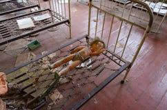Puppe auf Metallgitter des Betts in verlassenem Kindergarten in zerstörter Dorf Kopachi Tschornobyl NPP-Entfremdungszone, Ukraine lizenzfreies stockbild