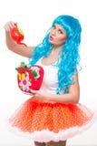 Puppe des jungen Mädchens mit dem blauen Haar wässernde künstliche Blumen lizenzfreies stockfoto