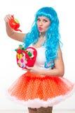 Puppe des jungen Mädchens mit dem blauen Haar wässernde künstliche Blumen stockfotografie