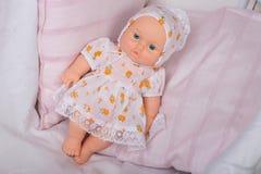 Puppe in einem Kleid auf einem rosa Kissen Stockbild