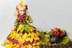 Puppe in einem Kleid hergestellt vom Herbstlaub mit einer Mannschaft von Kegeln Stockfoto