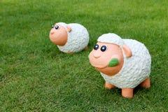 Puppe mit zwei Schafen auf der Wiese Stockfotografie