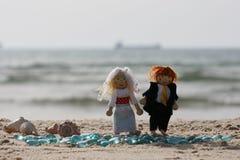 Puppen auf sandigem Strand Stockbilder