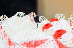 Puppen der Braut und des Bräutigams auf Hochzeitstorte Lizenzfreies Stockfoto