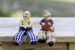 Puppen-Mann und Lesung und Stricken der alten Frau Stockfotografie
