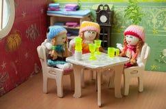 Puppen sitzen am Tisch Stockfotos